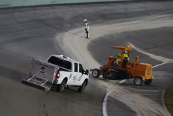 Track workers cleaning the track after the red flag