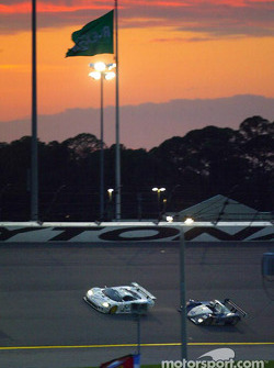 A pair of Grand-American sports cars race under the Rolex flag as the sun sets