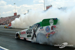 A double burn-out with John Force in the foreground
