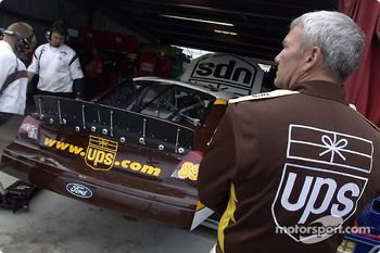Dale Jarrett standing by while the UPS crew work on the back up car after Jarrett crashed in practice