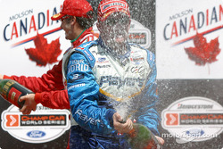 Things get ugly: Paul Tracy still sprays champagne while Michel Jourdain Jr. goes after the Molson Indy hostesses