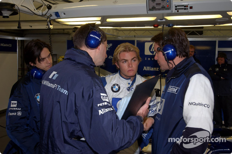 Nico Rosberg discusses with Sam Michael as Nelson A. Piquet watches