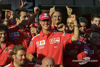 Michael Schumacher and Ferrari team members celebrate 2004 Constructors World Championship