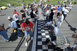 Fans autograph the start/finish line