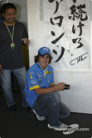 Fernando Alonso signs his autograph on a banner