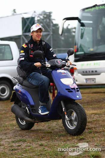 Sebastian Vettel, Red Bull Racing arriving at the circuit on his moped