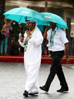 People use umbrellas in the rain, in the paddock