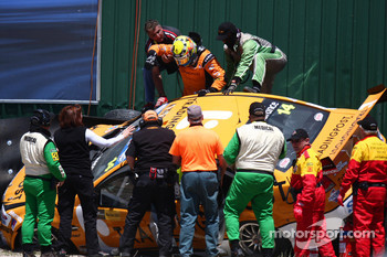 Jason Bright is helped from his car after a heavy crash during practice