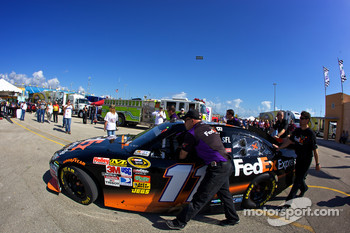 Joe Gibbs Racing Toyota team members push the car of Denny Hamlin to technical inspection