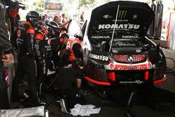 Team mechanics work on the car of Jamie Whincup, #1 TeamVodafone