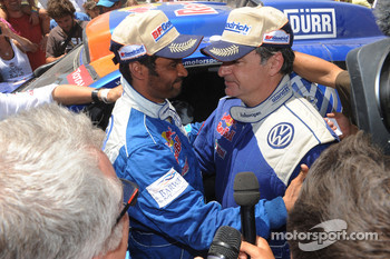 Car category winner Nasser Al Attiyah celebrates with Carlos Sainz