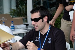 Dario Franchitti contemplates an object to be autographed
