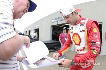 Helio Castroneves, Team Penske, signs autographs in Gasoline Alley during a rain delay. 