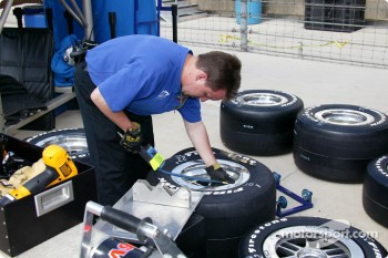 Team Menard crew member Trevor Mitchener prepares tires
