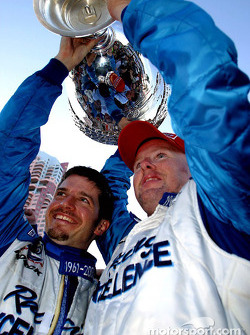Patrick Carpentier help teammate Paul Tracy hoist the Vanderbilt Cup