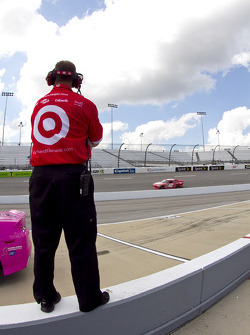 Juan Pablo Montoya's crew member watches as he takes to the track