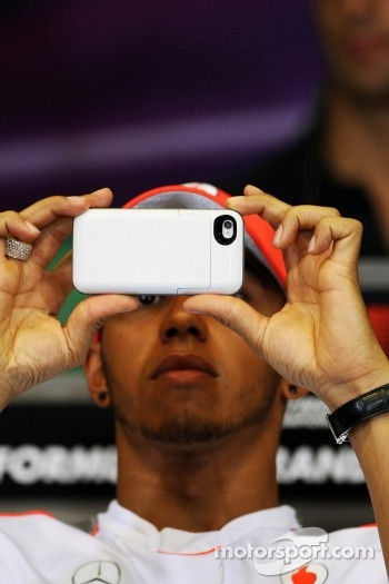Lewis Hamilton, McLaren in the FIA Press Conference using his camera phone