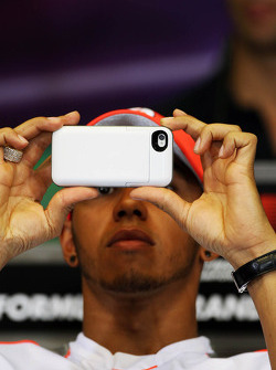 Lewis Hamilton, McLaren in the FIA Press Conference using his camera phone