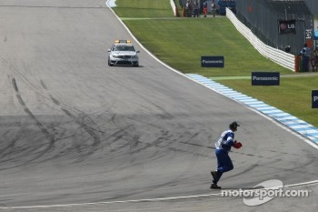 A marshal clears debris at the end of the opening lap of the race