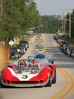 Race Cars parade into Elkhart Lake for the Friday Concours.  #3 1965 Lola T70 MkII : Johan Woerheide