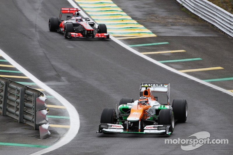 Nico Hulkenberg, Sahara Force India F1 leads Jenson Button, McLaren out of the pits