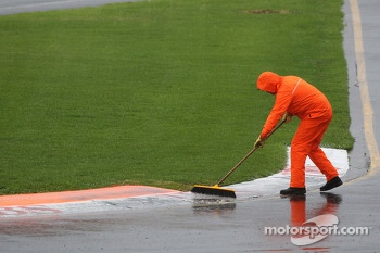 A marshal clears rain water from the circuit