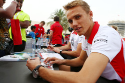 Max Chilton, Marussia F1 Team and team mate Jules Bianchi, Marussia F1 Team sign autographs for the fans