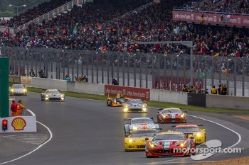GT cars under saftey car watched by huge crowds at Le Mans totaling approx 245,000 fans