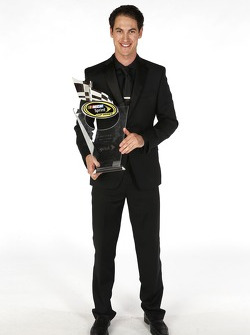 Joey Logano poses for a portrait with his eighth place trophy