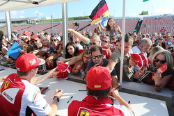Fernando Alonso, Ferrari and team mate Kimi Raikkonen, Ferrari sign autographs for the fans