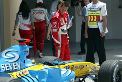 Michael Schumacher inspects the Renault F1 of Fernando Alonso