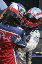 Race winner Heikki Kovalainen celebrates with Adam Carroll