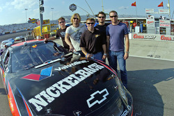 Scott Riggs stands alongside his car with Ryan Peake, Chad Kroeger, Daniel Adair and Mike Kroeger of the recording group