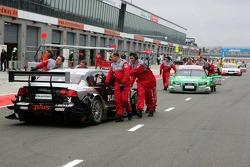 Mechanics push the cars to the Parc Fermé area