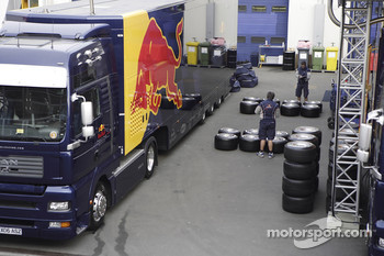 A Red Bull truck and engineers checking the tyres