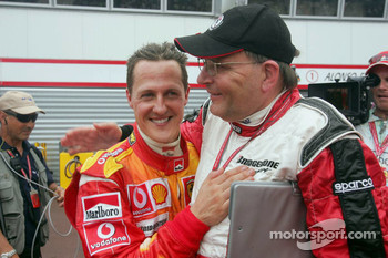 Michael Schumacher celebrates with Kees van de Grint, Bridgestone tire engineer