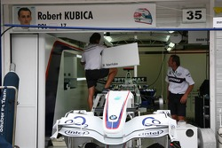 BMW Sauber team members apply Robert Kubica's garage sign