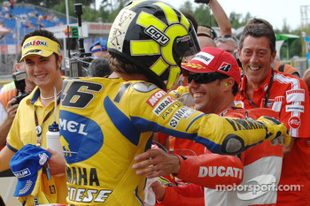Pole winner Valentino Rossi celebrates with Loris Capirossi
