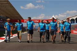 Heikki Kovalainen and Fernando Alonso walk the circuit with team members