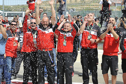 Ducati mechanics getting drenched under the podium