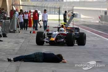 Mark Webber and a photographer lying down in the pitlane