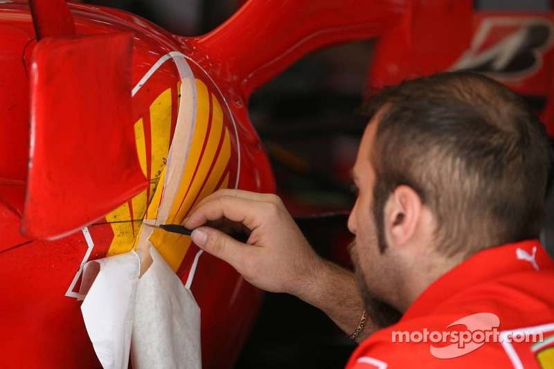 A Scuderia Ferrari mechanic touches up the sticker work