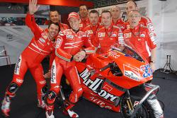 Loris Capirossi and Casey Stoner pose with Ducati team members