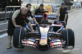 Red Bull Racing team members push the car on pitlane