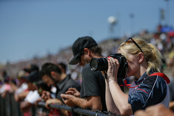 A photographer in the stands captures the action on track