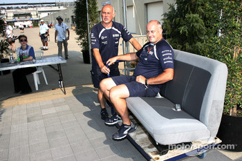 Williams F1 Team members with two car seats at the paddock gates