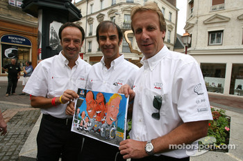 The winners of the 24 Hours of Le Mans 2006 Marco Werner, Frank Biela and Emanuele Pirro pose with a cartoon of themselves at the traditional winners manhole cover ceremony in downtown Le Mans