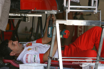 A Scuderia Ferrari team member works on the car