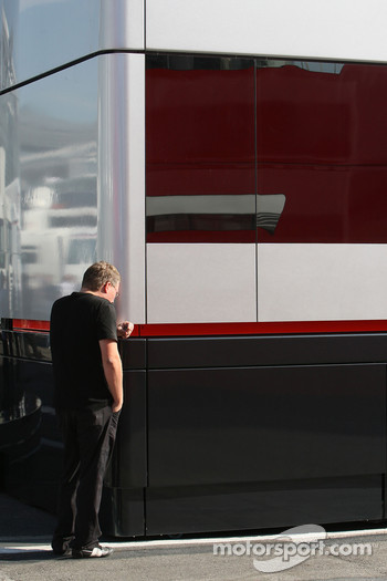 A man leaning against the McLaren Mercedes motorhome