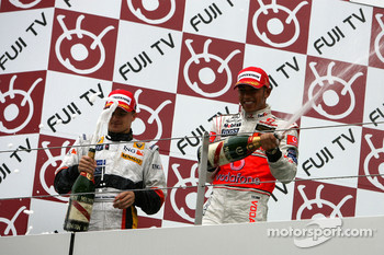 Podium: champagne for Lewis Hamilton and Heikki Kovalainen